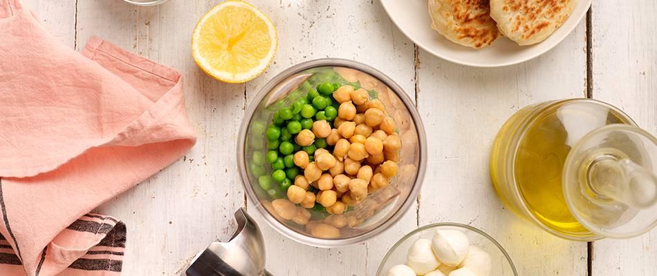 Garbanzos y guisantes en un bol, liquadora de mano y aceite de oliva