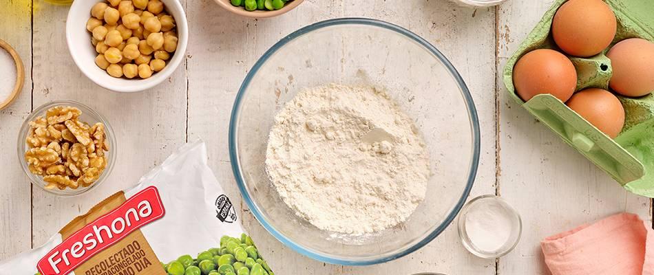 Harina de trigo en ból con huevos, nueces y guisantes finos en bolsa